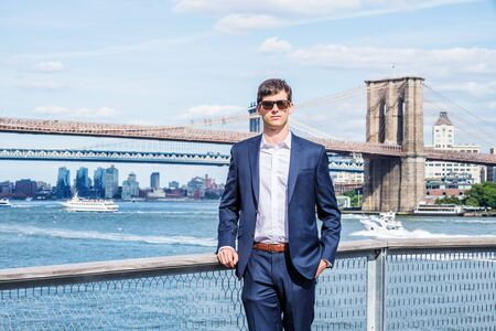 Young Handsome American Man traveling, relaxing in New York City, wearing blue suit, white shirt, sunglasses, standing by East River, looking forward. Manhattan, Brooklyn bridges, boats on background.