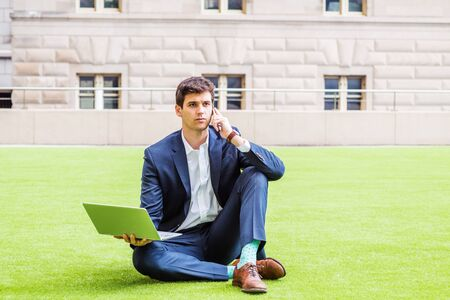 Young college student studying, working in New York, wearing blue suit, white shirt, brown leather shoes, sitting on green lawn outside office building, working on laptop computer, talking on phone. Foto de archivo - 134557204