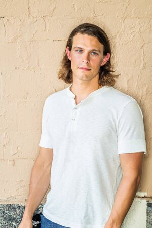Portrait of Young Handsome American Man with long dark brown hair in New York City, wearing white short sleeve shirt, standing against yellowish painted wall on street in hot summer, looking forward.