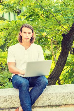 Young American Man with long dark brown hair working on laptop computer remotely outside in New York City, wearing white short sleeve shirt, sitting by green trees background, looking away, thinking. Фото со стока