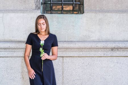 I love you, waiting for you. Young East European Woman wearing black short sleeve, v neck dress, holding white rose flower, standing by wall on street in New York City, looking down, sad, thinking.