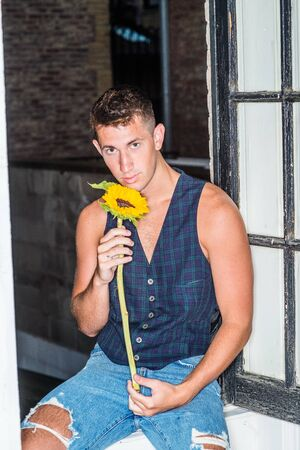 Young handsome man with short hair, wearing dark blue patterned vest, blue ripped Denim jeans with broken holes, sitting on frame of opening window inside at home, holding sunflower, looking at you.