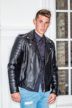 Portrait of Young Handsome Man at home in New York City. 20 years old man wearing black shirt, black leather jacket, standing by white wooden door, looking at you. Young Man Casual Fashion.