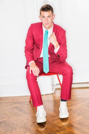 Young Businessman Fashion in New York City. 20 years old man with short hair, wearing red suit, white shirt, white sneakers, light green tie, siting on red chair by white background, looking at you.