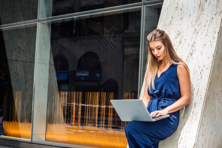 Young Eastern European American Woman working in New York, wearing blue sleeveless jumpsuit, standing against column outside office building, bending leg, looking down, working on laptop computer.