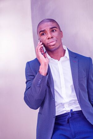 Young African American Business Man with short hair, talking on cell phone outside in New York City, wearing blue blazer, white shirt, standing against silver metal background. Color filtered effect.
