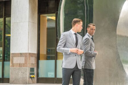 Young European Businessman Man wearing gray blazer, white shirt, black tie, black pants, hands buttoning, standing on street in front of metal mirror, turning around, looking at reflections, thinking.