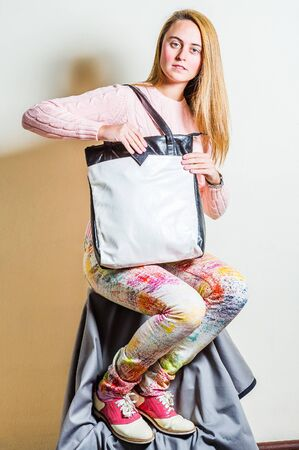 Young woman wearing long sleeve light pink knit sweater, light colorful pants, red and white leather sneakers, shoulder carrying white leather bag with black edge, hand holding cell phone into bag.