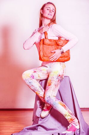 Young woman wearing long sleeve light pink knit sweater, light colorful pants, red and white leather sneakers, shoulder carrying orange brown leather bag. Color filtered effect
