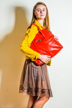 Young beautiful woman wearing long sleeve yellow corduroy jacket, dark brown mesh skirt, shoulder carrying red leather bag. Studio Shoot.