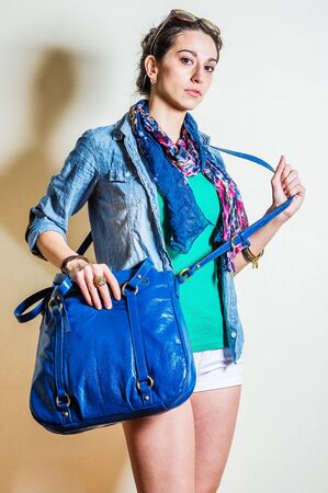 Young woman wearing blue long sleeve Denim shirt, green undershirt, white shorts, blue flowers patterned long scarf around neck, plastic sunglasses on head, shoulder carrying blue leather bag.