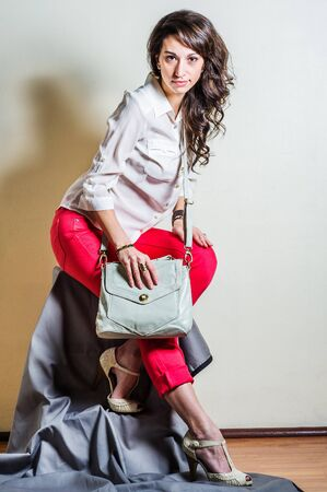 Young beautiful woman wearing white long sleeve shirt, red pants, light color sandals, shoulder carrying light gray leather bag, smiling. Studio shoot.