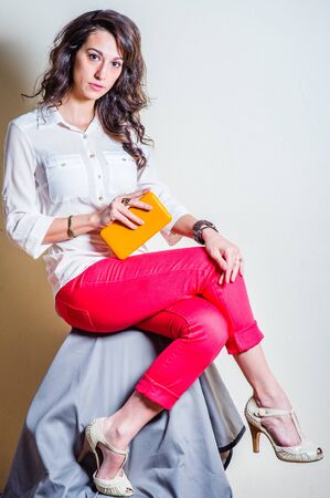 Young beautiful woman wearing white long sleeve shirt, red pants, light color sandals, one hand holding small yellow leather purse, looking at you. Studio shoot. Foto de archivo