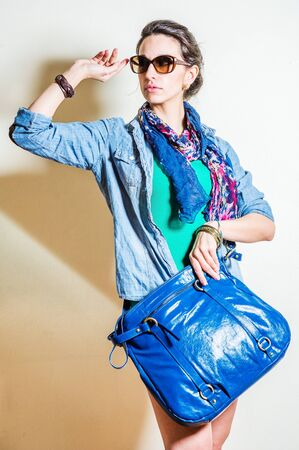 Young woman wearing blue long sleeve Denim shirt, unbuttoned, green undershirt, blue long scarf around neck, plastic brown sunglasses, holding blue leather bag, raising arm, looking away. Studio Shoot