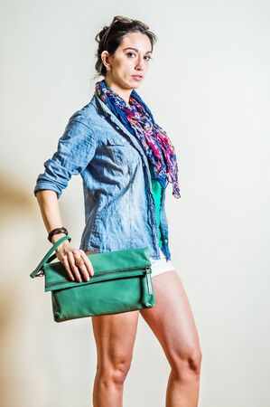 Young woman wearing blue long sleeve Denim shirt, white shorts, blue flowers patterned long scarf around neck, plastic brown sunglasses on head, hand holding green leather purses. Studio Shoot. Foto de archivo