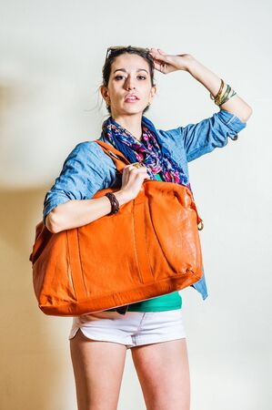 Young woman wearing blue long sleeve Denim shirt, white shorts, blue flowers patterned long scarf around neck, holding plastic sunglasses on head, shoulder carrying big brown leather bag. Studio Shoot.