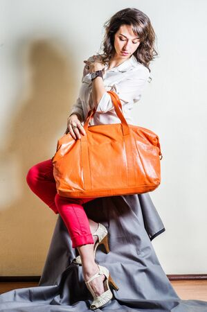 Young beautiful woman wearing white long sleeve shirt, red pants, light color sandals, arm carrying brown big leather bag. Studio shoot. Foto de archivo