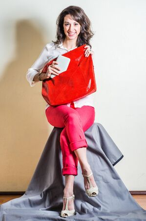 Young beautiful woman wearing white long sleeve shirt, red pants, light color sandals, carrying red big leather bag, hand holding white leather purse into bag, smiling. Studio shoot.