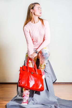 Young woman wearing long sleeve light pink knit sweater, light colorful pants, red and white leather sneakers, black wristwatch, hand holding bright red leather bag, looking away. Studio Shoot.