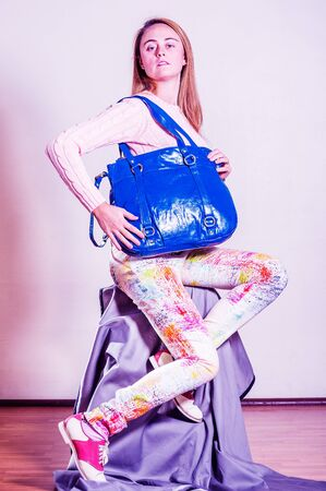 Young woman wearing long sleeve light pink knit sweater, light colorful pants, red and white leather sneakers, shoulder carrying bright blue leather bag. Color filtered effect. Foto de archivo