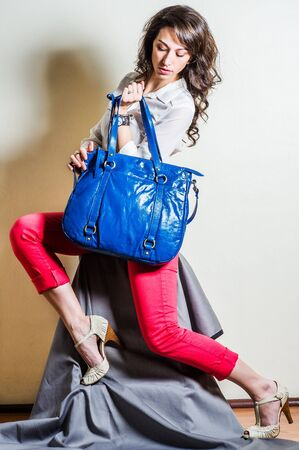 Young beautiful woman wearing white long sleeve shirt, red pants, light color sandals, hand carrying blue big leather bag. Studio shoot.