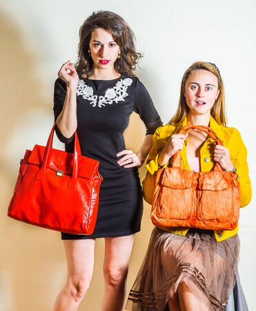 Two young beautiful women, one wearing long sleeve yellow corduroy jacket, dark brown mesh skirt, holding orange brown leather bag, other wearing black dress, arm carrying red leather bag. Studio Shot