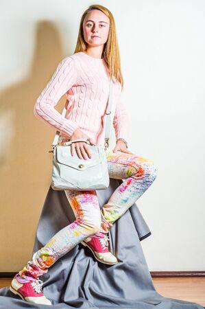 Young woman wearing long sleeve light pink knit sweater, light colorful pants, red and white leather sneakers, shoulder carrying, hand holding light gray leather bag. Studio Shoot.