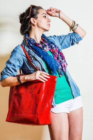 Young woman wearing blue long sleeve Denim shirt, white shorts, blue flowers patterned long scarf around neck, plastic sunglasses on head, shoulder carrying red leather bag, hand touching forehead. Foto de archivo