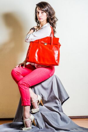 Young beautiful woman wearing white long sleeve shirt, red pants, light color sandals, shoulder carrying bright red big leather bag. Studio shoot.