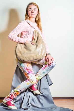 Young woman wearing long sleeve light pink knit sweater, light colorful pants, red and white leather sneakers, shoulder carrying beige leather bag. Studio Shoot. Foto de archivo