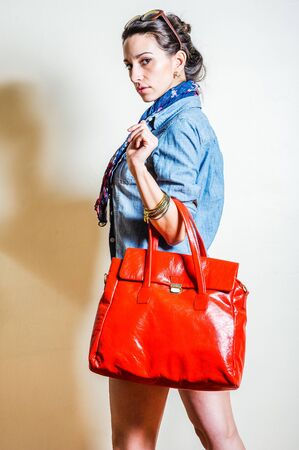 Young woman wearing blue long sleeve Denim shirt,  blue flowers patterned long scarf around neck, plastic sunglasses on head, carrying big red leather bag with arm. Studio Shoot. Side View.