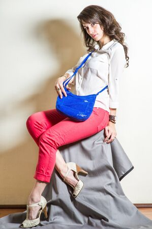 Young beautiful woman wearing white long sleeve shirt, red pants, light color sandals, carrying blue shoulder leather bag. Studio shoot. Foto de archivo