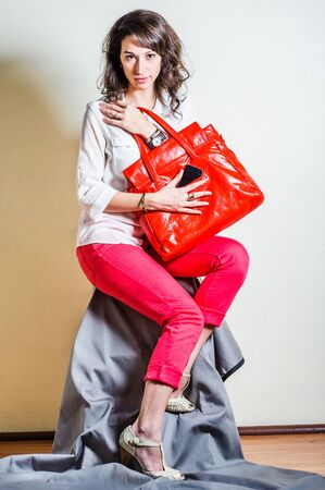 Young beautiful woman wearing white long sleeve shirt, red pants, light color sandals, holding bright red leather bag, hand putting cell phone into bag. Studio shoot. Foto de archivo