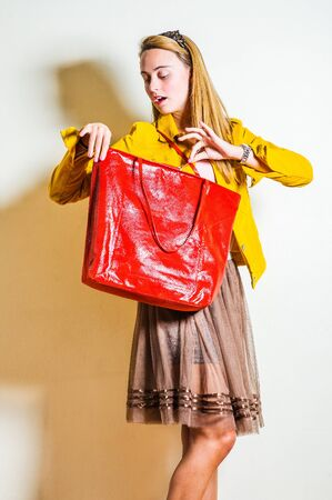 Young beautiful woman wearing long sleeve yellow corduroy jacket, dark brown mesh skirt, shoulder carrying red leather bag, hand opening bag with zipper, turning head, looking inside. Studio Shoot