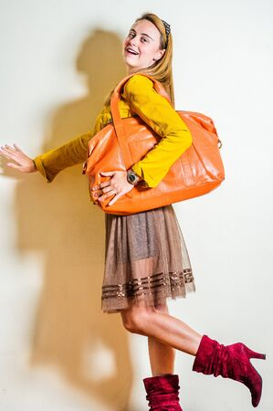 Young beautiful woman wearing long sleeve yellow corduroy jacket, dark brown mesh skirt, red boots, shoulder carrying brown leather bag, smiling. Studio Shoot. Foto de archivo