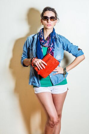 Young woman wearing blue long sleeve Denim shirt, unbuttoned, green undershirt, white shorts, blue long scarf around neck, plastic brown sunglasses, holding red leather purse, hand resting on waist.