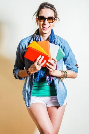 Young woman wearing blue long sleeve Denim shirt, unbuttoned, green undershirt, white shorts, blue long scarf around neck, plastic brown sunglasses, two hands holding five colorful purses, smiling. Foto de archivo