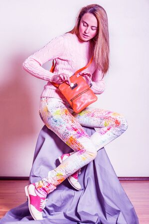 Young woman wearing light pink knit sweater, colorful pants, red and white leather sneakers, shoulder carrying brown leather bag, looking down, fingers picking coin into bag. Color filtered effect. Foto de archivo