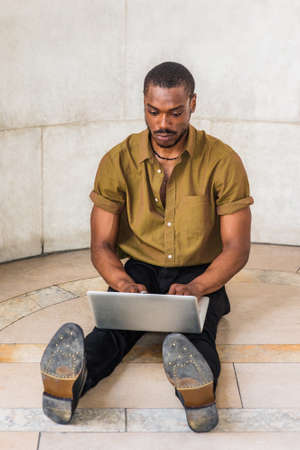 Young African American Man studying in New York City, wearing green short sleeve shirt, black pants, leather shoes, stretching legs, sitting on marble ground on campus, working on laptop computer.