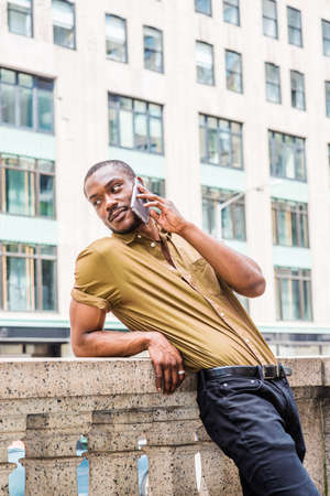 Young African American Man with beard, wearing green short sleeve shirt, standing against half wall by street with high building in Manhattan of New York City, turning around, talking on cell phone. Archivio Fotografico
