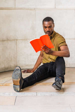 Young African American Male College Student with beard studying in New York City, wearing green short sleeve shirt, black pants, leather shoes, sitting on marble ground on campus, reading red book.