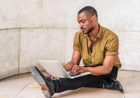 Young African American Man with beard studying in New York, wearing green short sleeve shirt, black pants, leather shoes, sitting legs crossed on marble ground on campus, working on laptop computer.