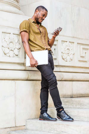Young African American Man studying in New York, wearing green short sleeve shirt, black pants, leather shoes, carrying laptop computer, standing against white marble wall, texting on cell phone.