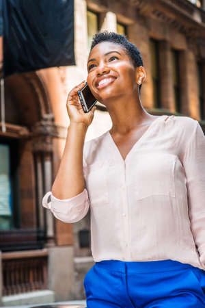 Young Happy African American Woman with short afro hair, traveling in New York City, wearing pink v neck shirt, blue pants, walking on street, talking on cell phone, looking up, smiling.