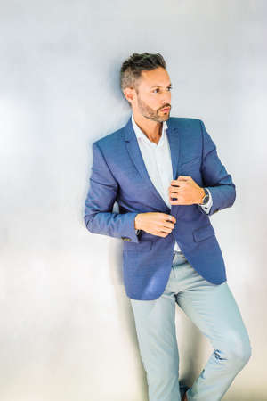 Portrait of Young Businessman in New York City. Young European Businessman with beard, wearing white shirt, blue jacket, standing against silver metal wall, hands buttoning, looking, thinking.