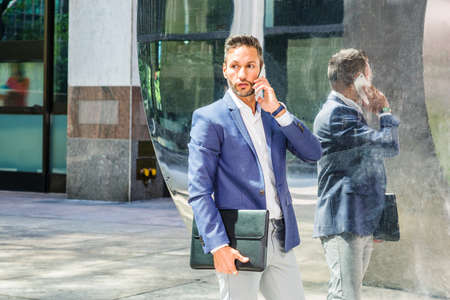 Young European Businessman traveling to work in New York City, with beard, little gray hair, wearing blue jacket, holding black leather briefcase, standing by mirror on street, talking on cell phone. 版權商用圖片