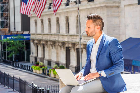 Young European Businessman with beard traveling, working in New York City, wearing blue blazer, sitting on street outside office building, working on laptop computer, looking up, thinking.