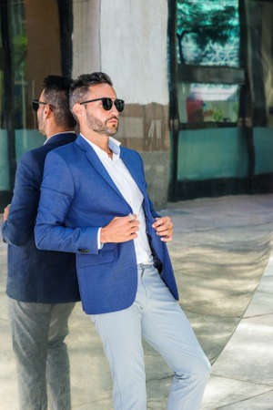 Thinking By Mirror. Young European Businessman with beard, wearing white shirt, blue jacket, sunglasses, standing back against metal mirror on street in New York City, thinking, lost in thought.