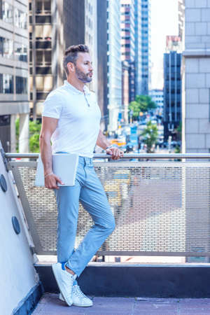 Young Serious European Businessman with beard, little gray hair, wearing white shirt, light blue pants, white sneakers, holding laptop computer, standing by railing on balcony in New York City.