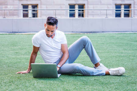 Young European Man studying, working in New York City, with beard, little gray hair, wearing white short sleeve shirt, gray pants, sneakers, sitting on green lawn, reading, working on laptop computer.